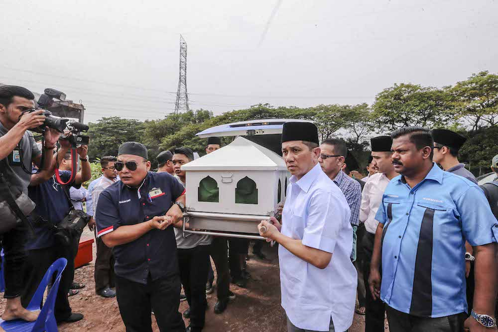 Economic Affairs Minister Datuk Seri Mohamed Azmin Ali acts as a pallbearer at the funeral of late Sungai Kandis assemblyman Mat Shuhaimi Shafiei at Shah Alam Muslim cemetery. — Picture by Firdaus Latif